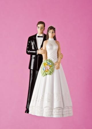 wedding cake: Wedding Figurines towards pink background Stock Photo