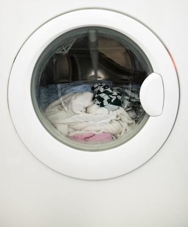 lavadora con ropa: Primer plano de una máquina de lavandería