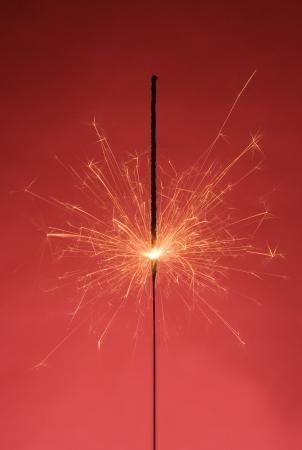 Burning Sparkler on red background