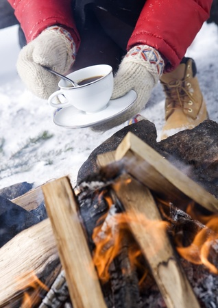 Holding a cup of Coffee with winter gloves photo