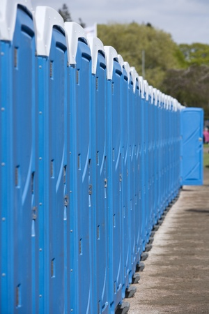 personal perspective: Row of Blue Portable Toilets Stock Photo