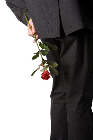 Man holding a red rose behind his back photo