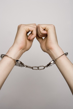 Unreconizable teenager with handcuffs on grey background photo