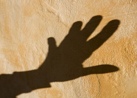 Shadow of a hand on the wall photo