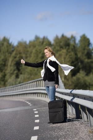 Autostop mujer sola en el lado de la carretera