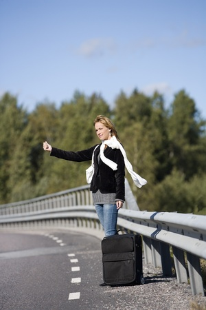 Hitchhiking woman alone at the side of the road photo