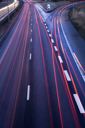single lane road: Highway with moving cars at dawn
