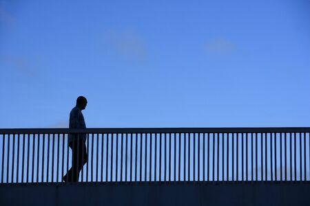 Silhouette of a walking man on a bridge photo