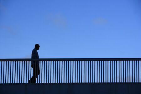 elevated walkway: Silhouette of a walking man on a bridge