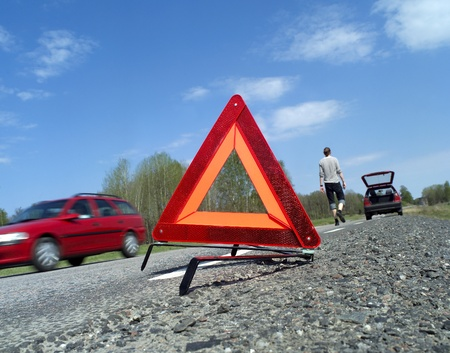 Warning traingle at the side of the road Imagens