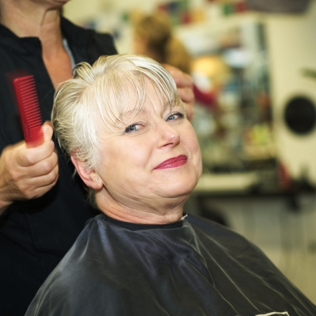 Older woman at the Hairdressers studion Foto de archivo
