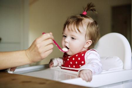 meisje eten: Jonge Meisje van de baby eten in de keuken Stockfoto