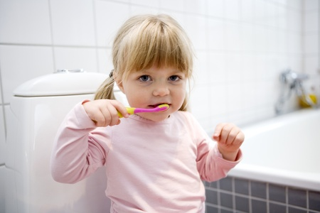 Baby Girl with toothbrush in the bathroom photo
