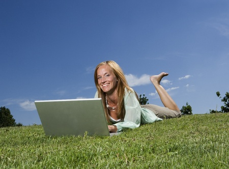 Woman with computer in the grass towards blue sky Stock Photo - 12899156