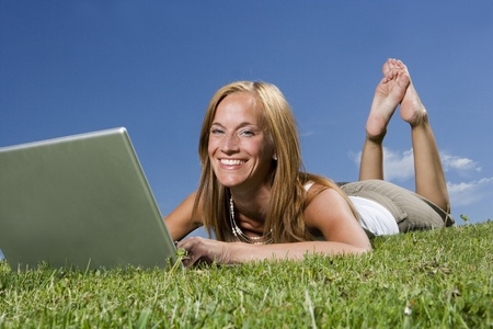 Woman with computer in the grass towards blue sky photo
