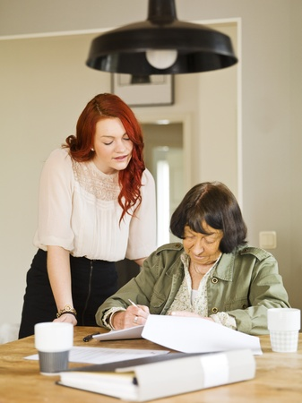Young woman helping her Grandmother with paperwork photo