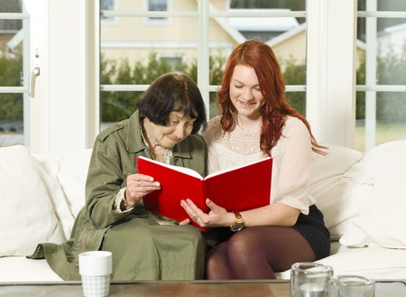 Young woman and her Grandmother looking in the Photo Album Stock Photo - 12899304