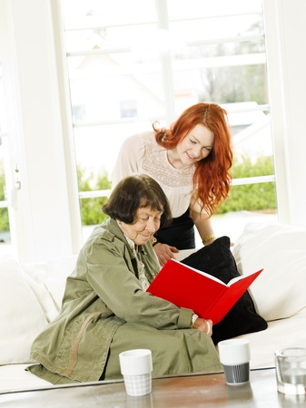 Young woman and her Grandmother looking in the Photo Album photo