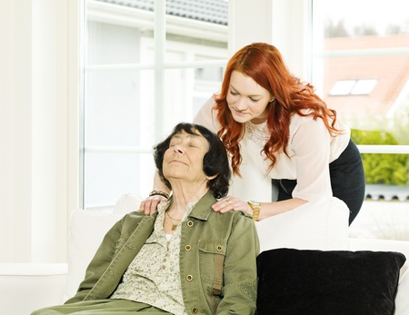 Young woman giving massage to her Grandmother photo