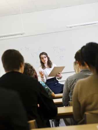 Lehrerin vor Schülern im Klassenzimmer Lizenzfreie Bilder