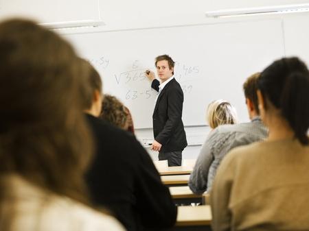 high school teacher: Schoolteacher in front of pupils in the classroom Stock Photo