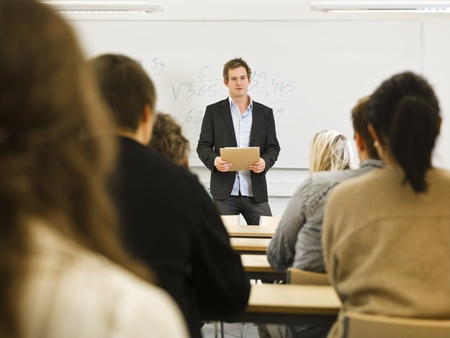 adult classroom: Schoolteacher in front of pupils in the classroom Stock Photo
