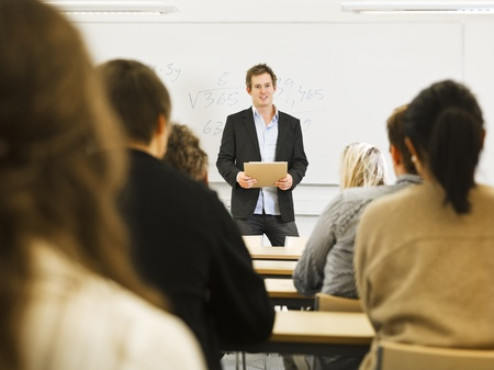 Schoolteacher in front of pupils in the classroom Standard-Bild