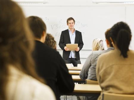 Onderwijzer in de voorkant van de leerlingen in de klas