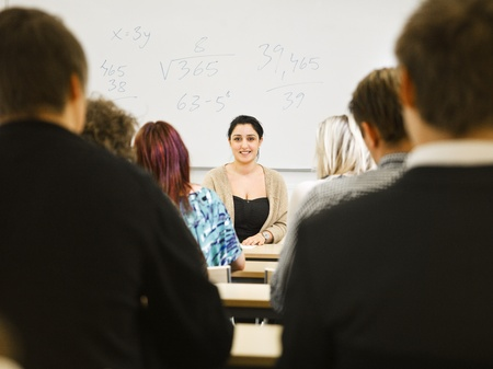 Schoolteacher in front of pupils in the classroom Stock Photo - 13125198