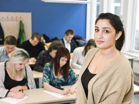 adult only: Schoolteacher in front of pupils in the classroom Stock Photo