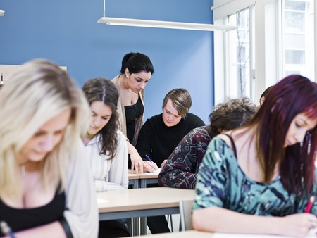Teacher and young Adult students in the classroom Stock Photo - 13125010