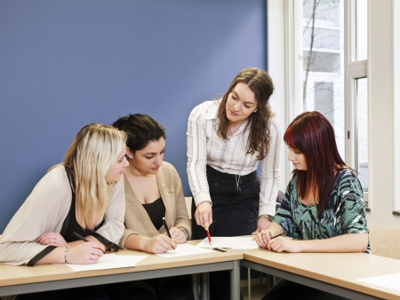 maestro dando clases: Cuatro chicas trabajo en grupo en el aula