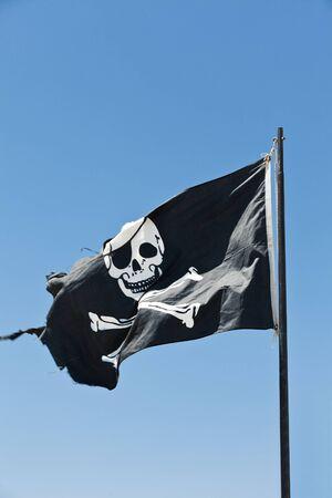 drapeau pirate: Drapeau de pirate vers le ciel bleu
