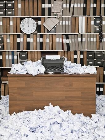 habitacion desordenada: Oficina con m�quina de escribir vintage y un mont�n de papeles Foto de archivo