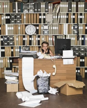 oficina desordenada: Chica joven cansada en una oficina desordenada