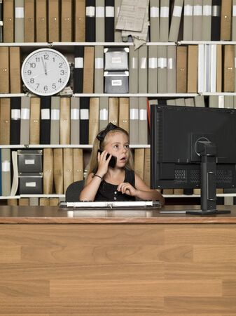 Young Buiness girl on the phone in front of a computer Stock Photo - 14903412