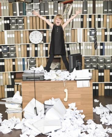 oficina desordenada: Chica joven de negocios feliz en una oficina desordenada Foto de archivo