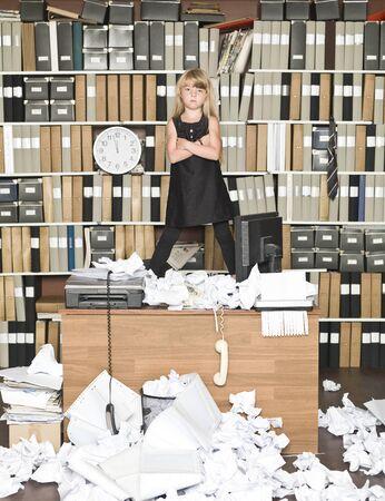 messy office: Affari ragazza seria in un ufficio disordinato Archivio Fotografico