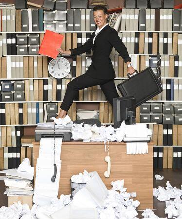 oficina desordenada: Empresaria feliz en una oficina desordenada Foto de archivo