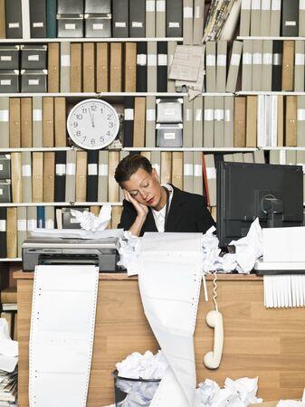 messy office: Stanco di affari presso l'ufficio disordinato