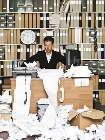 oficina desordenada: Empresaria frustrada en una oficina desordenada Foto de archivo