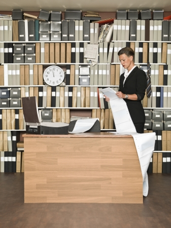 fax machine: Businesswoman by the fax machine Stock Photo