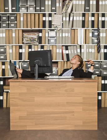Relaxed Businesswoman smoking at the office Stock Photo - 14903436