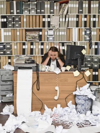 oficina desordenada: Empresaria cansada en una oficina desordenada
