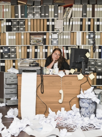 Tired Businesswoman in a messy office Stock Photo - 14903418
