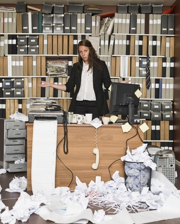 Tired Businesswoman in a messy office Stock Photo - 14903437