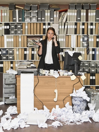 Businesswoman on the phone at the messy office Stock Photo - 14903443