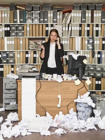 messy office: Donna di affari sul telefono in ufficio disordinato