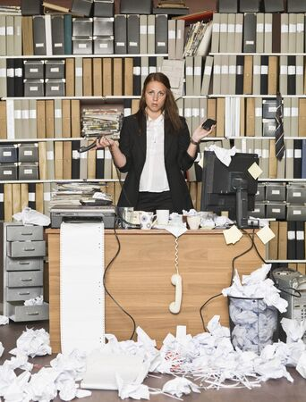 Sour businesswoman in a messy office Stock Photo - 14903439