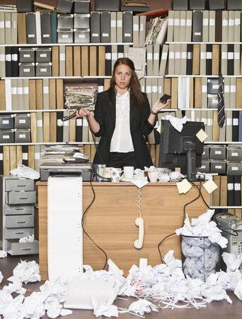 messy office: Sour imprenditrice in un ufficio disordinato